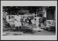 Betty Tyler pushing wheelbarrow, Marshall Tyler, Alice Tyler (Fowler), and Judy Tyler in wheelbarrow