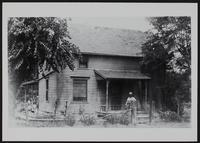 Man in front of farmhouse